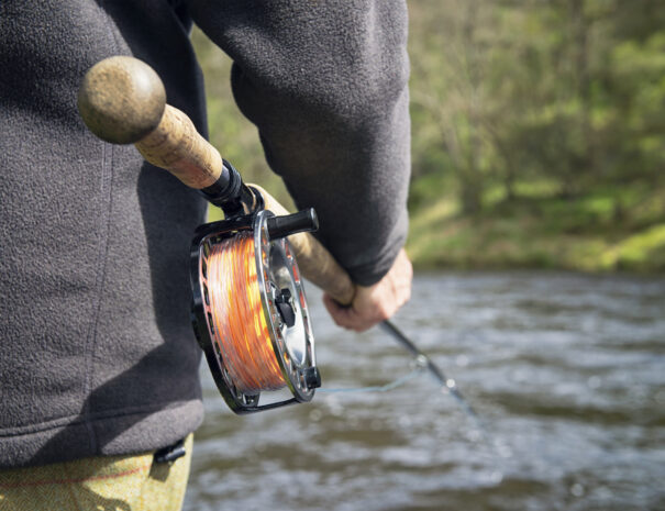 A man fly fishing in a Scottish river.