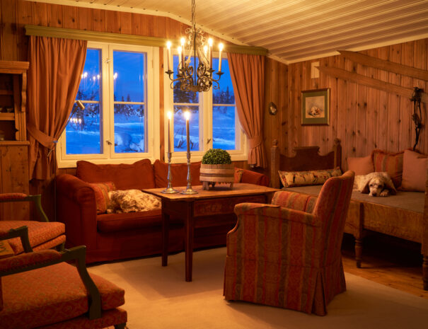 Living room interior at dusk lit by candlelight with two English setters sleeping, mountain landscape with deep snow visible through the window. Norway