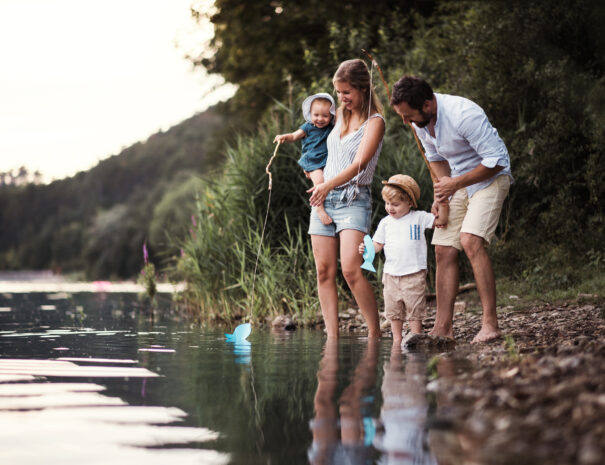 A young family with two toddler children spending time outdoors by the river in summer.